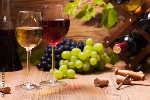 Foto Glasses of red and white wine, served with grapes
