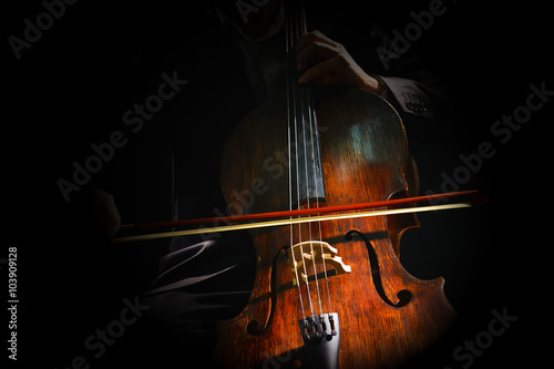 Foto Man playing on cello on dark background