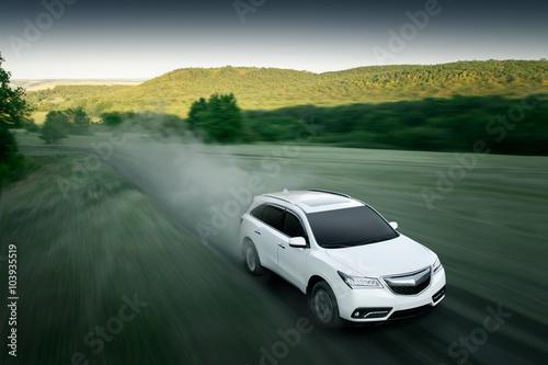 Fotografia, Obraz  Modern car fast drive on dirt road at sunset