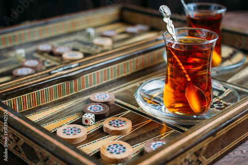Obraz na plátně Turkish sweets and tea on the backgammon Board