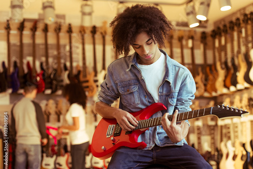 Photo Stands Music store Man playing electric guitar