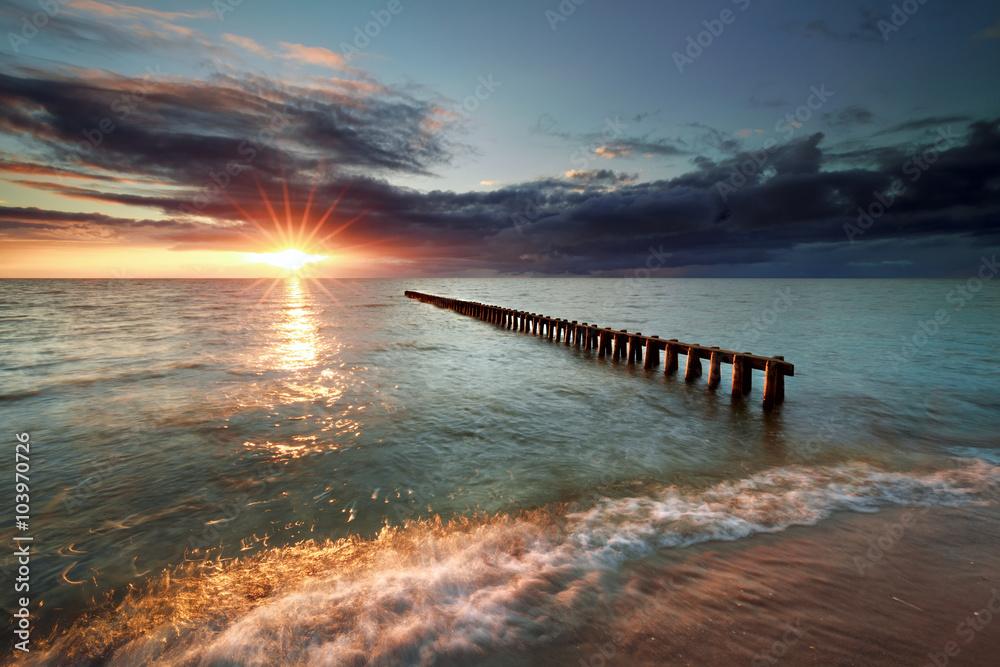 Fototapeta sunset over breakwater in Ijsselmeer lake