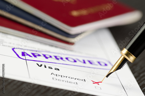 Fotografie, Obraz  Visa application approved, close up shot of a form, passports and pen