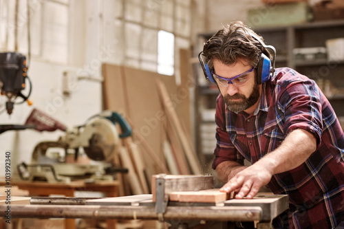 Fotografia  Carpenter working with machinery cutting a wooden plank
