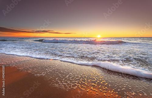 Photographie Lever de soleil coloré plage océan avec un ciel bleu profond et des rayons de soleil