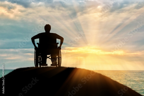 Valokuva  Silhouette of disabled person in a wheelchair