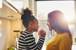 Leinwandbild Motiv Black woman and little daughter smiling