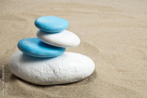 Photo sur Toile Zen pierres a sable Pile de galet en équilibre sur du sable aux couleurs bleu et blanc de certains drapeaux