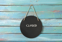 Closed Sign Hanging On Blue Ba...