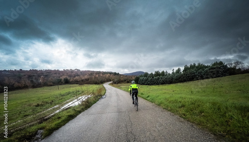 Foto op Plexiglas Fietsen man on a bicycle ride along a mountain road during a storm