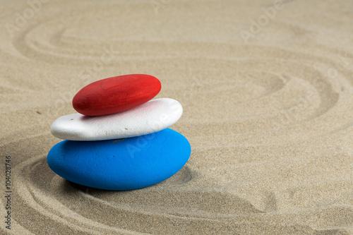 Fotografia  Pile de pierres colorés, bleu, blanc, rouge aux couleurs de plusieurs drapeaux n