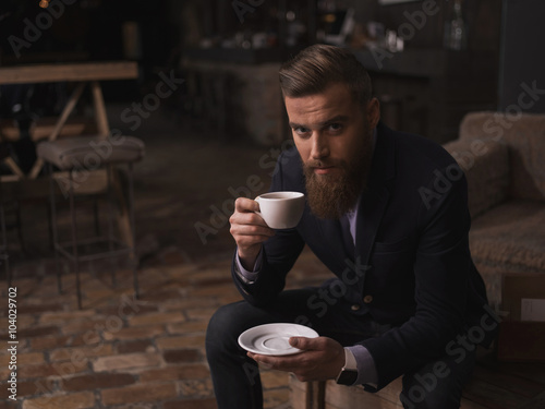 Carta da parati Attractive bearded businessman is enjoying hot coffee