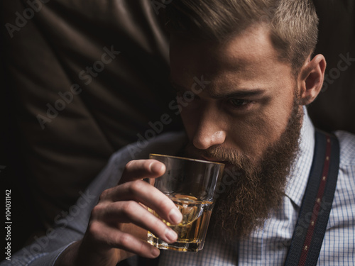 Cheerful bearded businessman is drinking expensive whisky Tableau sur Toile