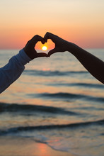 Couple Doing Heart Shape With Their Hands On Beachside