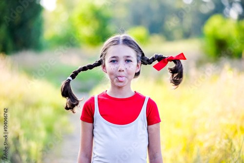 Photo  girl with pigtails imagines the summer on the nature