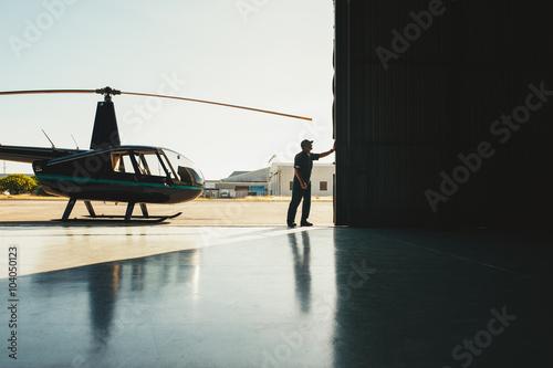 fototapeta na szkło Mechanic opening the door of a airplane hangar