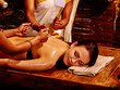 Two masseuses do massage in four hands into India spa salon.