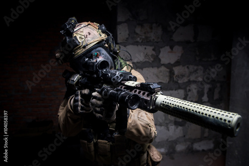 Fotografia  Special Forces soldier in protective uniform aimingg from rifle/ Special forces soldier wearing helmet and mask holding rifle with silencer aiming at camera