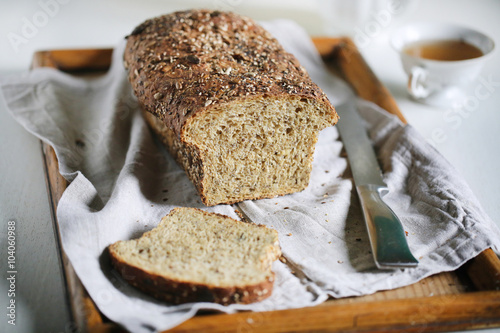 Fotografie, Obraz  Seed crust multi grain rustic sourdough loaf, sliced at breakfast