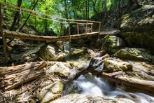 Wooden Bridge Through The Forest River
