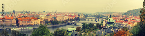 Panoramic view of old beautiful Prague city with red roofs and bridges through the river Vltava, vintage retro autumn hipster background