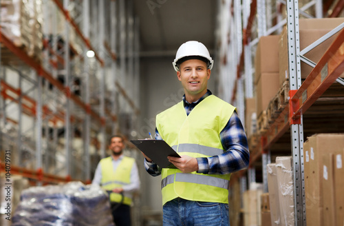 Obraz man with clipboard in safety vest at warehouse - fototapety do salonu