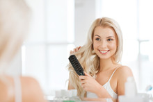 Happy Woman Brushing Hair With...