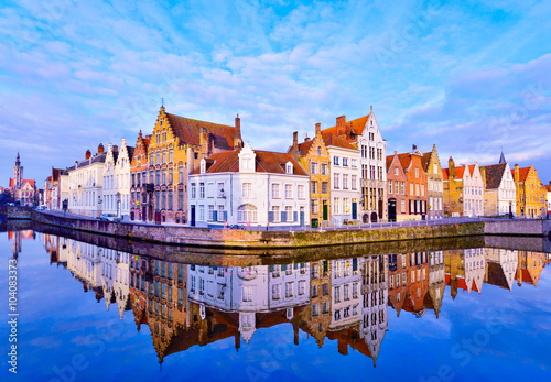 Traditional architecture in Bruges town, reflected in water at sunrise