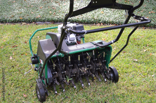 Fényképezés  Lawn aeration machine with grass plug stuck in the stem