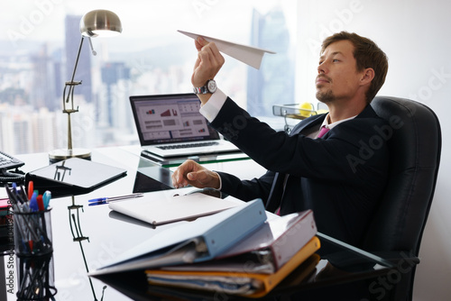 Fotografie, Obraz  Bored White Collar Worker Throwing Paper Airplane In Office
