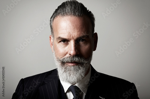 Closeup portrait of adult businessman wearing trendy suit against the empty wall. Horizontal
