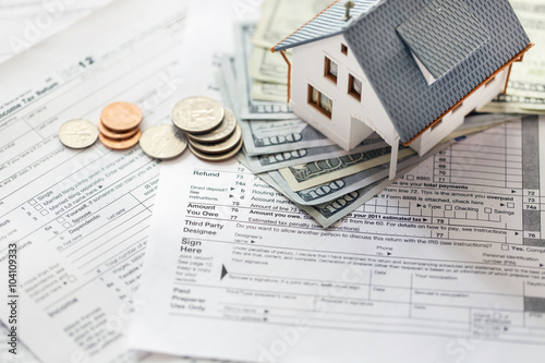 Fototapeta Miniature house with money on tax papers obraz