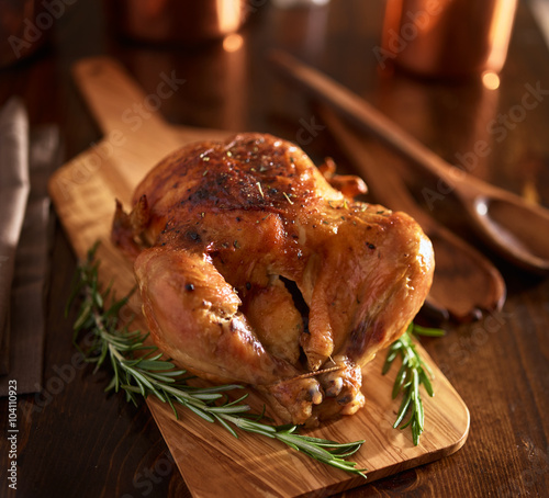Keuken foto achterwand Kip rotisserie chicken on wooden serving tray with herbs and rosemary