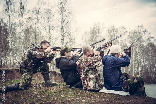 Foto op Aluminium Jacht group of people with guns aimed to the sky and prepared to make a shot