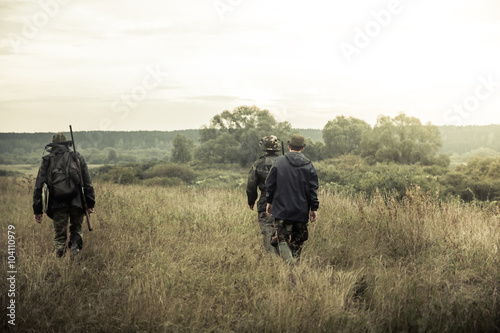 Foto op Canvas Jacht group of people going up in the early morning in a rural field through the tall grass during hunting