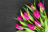 Fototapeta Kwiaty - Bukiet różowych tulipanów leżący na czarnych deskach.