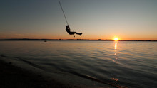 Boy Swings From Rope Over Lake Champlain In Vermont At Sunset