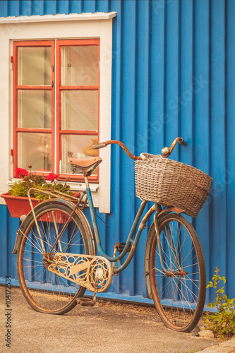 Old rusty lady bicycle in front of a Swedish house - 104172534