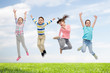 happy children jumping in air over sky and grass