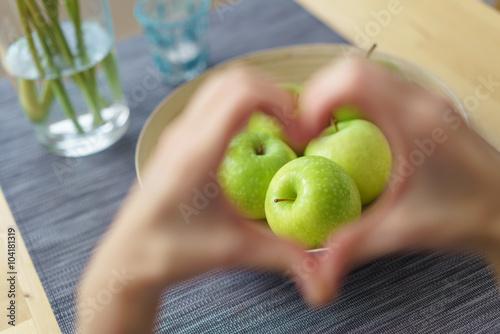 Fotografía  Frau zeigt ein Herz mit den Händen mit äpfeln im fokus
