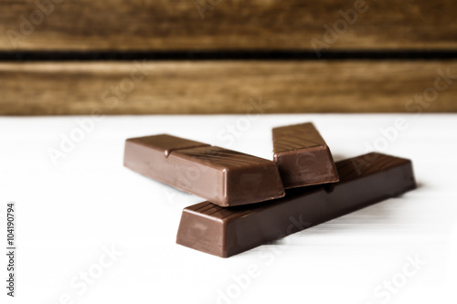 Aluminium Prints Grocery Three chocolate bars on white base and wooden background
