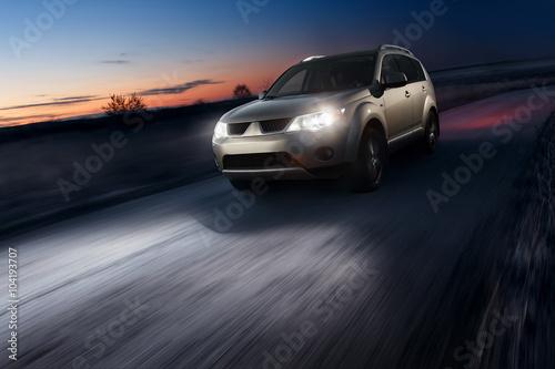 Car fast speed drive on asphalt road at dusk