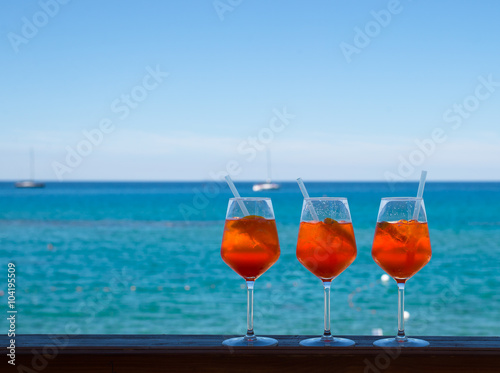 Refreshing aperitif Aperol spritz on a background of blue sea an