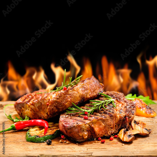 Grilled beef steak with flames - 104218900