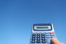 Electronic Calculator And The Hand In The Blue Sky