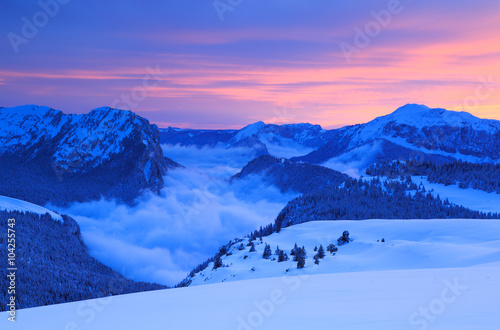 Fototapeta Clouds in the valley of a mountain range in French Alps during a colorful sunset