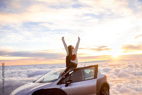 Fotografie, Tablou Young woman in sweater with heart shape rising hands sitting on the car roof above the clouds on the sunrise