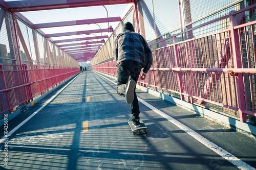 Fotografie, Obraz  Long shadow of a skateboarder cruising through crosswalk