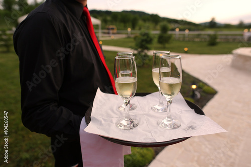 Valokuva  waiter holding four champagne glasses on a tray