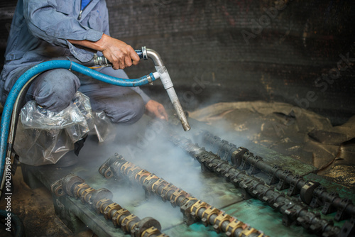 Fényképezés Worker is cleaning the machine equipment by using the air pressure sand / dryice